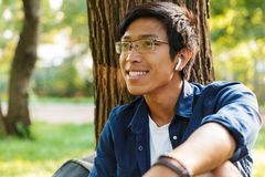 Happy asian male student in eyeglasses looking away royalty free stock image