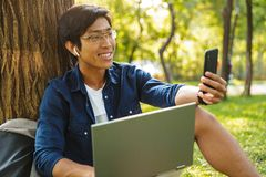 Happy asian male student in eyeglasses making selfie on smartphone stock image