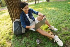 Happy asian male student in eyeglasses using laptop computer stock image