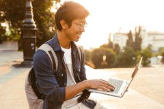 Happy asian male student in eyeglasses using laptop computer stock photos