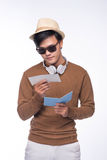 Happy asian male tourist holding passport over grey background Stock Photo