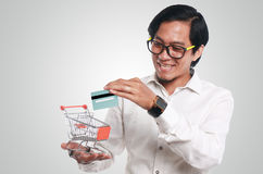 Happy Asian Man With Credit Card and Trolley. Photo image portrait of a funny young Asian businessman looking happy and smiling while putting a credit card into Royalty Free Stock Images