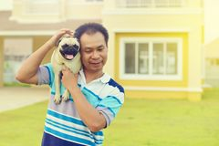 Happy Asian man with dog. Happy Asian man playing with his dog in garden stock photo