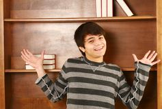 Happy asian man in front of book shelf Stock Photos