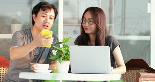 Happy asian man with girl friend using cell phone and laptop computer together. Happy asian man with girl friend are using cell phone and laptop computer stock video footage