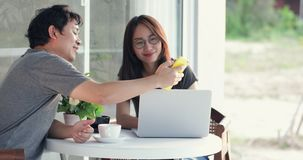 Happy asian man with girl friend using cell phone and laptop computer together. Happy asian man with girl friend are using cell phone and laptop computer stock video