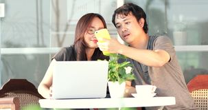 Happy asian man with girl friend using cell phone and laptop computer together. Happy asian man with girl friend are using cell phone and laptop computer stock footage