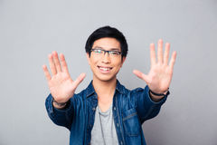 Happy asian man in glasses making stop gesture Stock Images