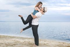 Happy asian man in hat hugging his girlfriend on the beach. Summer vacation royalty free stock photos