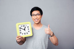 Happy asian man holding big clock and showing thumb up Royalty Free Stock Photography