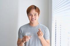 Happy asian man holding omega 3 vitamin pill at home Royalty Free Stock Photography