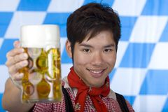 Happy Asian man holds Oktoberfest beer stein Stock Images