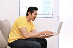 Happy asian man with laptop sitting on the couch Royalty Free Stock Images