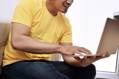 Happy asian man with laptop sitting on the couch Stock Photos