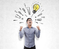 Happy Asian man, light bulb and exclamation marks Stock Photo