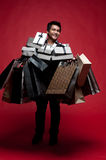 Happy Asian Man with lots goods in hands Royalty Free Stock Photography