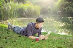 Happy asian man lying on the grass and write something on the bo. Ok at park stock photos