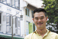 Happy Asian man out walking in the city. Royalty Free Stock Image