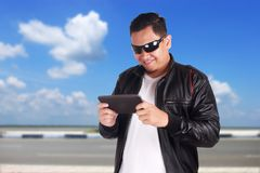 Happy Asian Man Playing Online Game on Tablet. Portrait of happy smiling attractive young Asian man playing online games on his tablet, excited winning gesture Royalty Free Stock Images