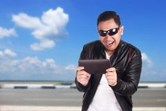 Happy Asian Man Playing Online Game on Tablet. Portrait of happy smiling attractive young Asian man playing online games on his tablet, excited winning gesture Royalty Free Stock Image