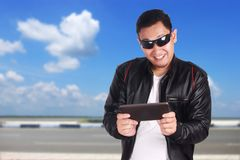 Happy Asian Man Playing Online Game on Tablet. Portrait of happy smiling attractive young Asian man playing online games on his tablet, excited winning gesture Stock Image