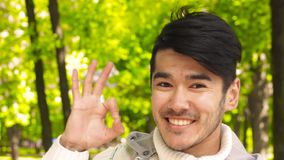Happy asian man show OK sign to camera stock footage