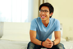 Happy asian man sitting on the bed Stock Images