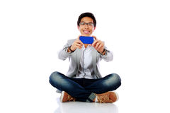Happy asian man sitting on the floor a Royalty Free Stock Photography