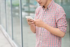 Happy asian man smiling as he reads a text message standing outs. Ide the office Stock Photos