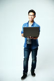 Happy asian man standing with laptop Royalty Free Stock Image
