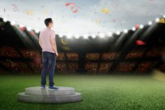Happy asian man standing on podium with confetti. In the air stock image