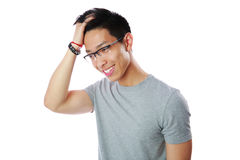 Happy asian man touches his head. Portrait of a happy asian man touches his head over white background stock photography