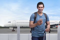 Happy asian man traveler standing with bag and mobile phone. In airport Stock Photos