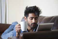 Happy Asian man using digital tablet at home on sofa. Stock Image