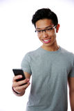 Happy asian man using smartphone Stock Images