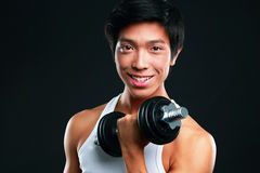 Happy asian man working out with dumbbells. On black backgroung Stock Photo