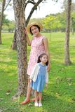 Happy Asian mom and daughter relaxing in the summer park stock images