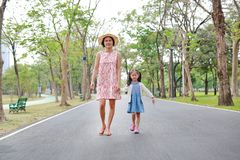 Happy Asian mom and daughter walking on street in the summer park royalty free stock photography