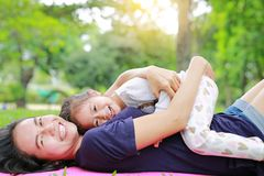 Happy Asian mom embrace her daughter lying in the green garden with looking camera. Funny mother and child girl playing in summer. Park royalty free stock photo