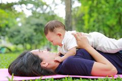 Free Happy Asian Mom Embrace Her Son Lying In The Green Garden. Funny Mother And Infant Baby Boy Playing In Summer Park Royalty Free Stock Images - 131462099