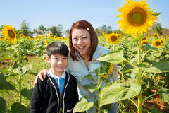 Happy asian mom with her son in sunflower flower field. Royalty Free Stock Photos