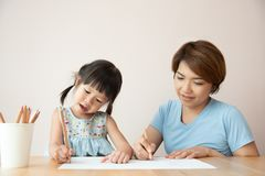 Happy Asian Mother and daughter drawing together. royalty free stock images