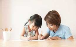 Happy Asian Mother and daughter drawing together stock image