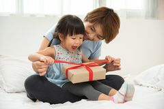 Child daughter unwrapping gift box with her mom. royalty free stock photography