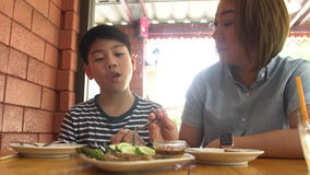 Happy Asian mother with her son eating lunch at home. Happy asian family enjoy with meal stock video footage