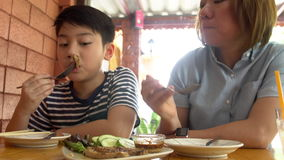 Happy Asian mother with her son eating lunch at home. Happy asian family enjoy with meal stock video