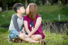 Happy Asian mother with her son at park Stock Photos