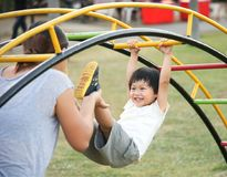 Happy mother holding her child hanging on playground royalty free stock photo