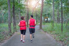 Happy asian mother and son jogging running in the park stock photo