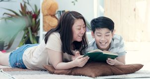 Asian mother with son reading book together with smile face. Happy Asian mother with son reading book together with smile face. in the living room. Mom teaches stock image